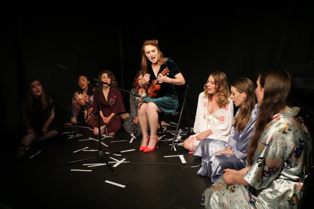 Ferrero Rochelle sits in the centre with a ukulele, she is singing. The troupe sit in a semi-circle at her feet, dressed in silk dressing gowns, also singing.