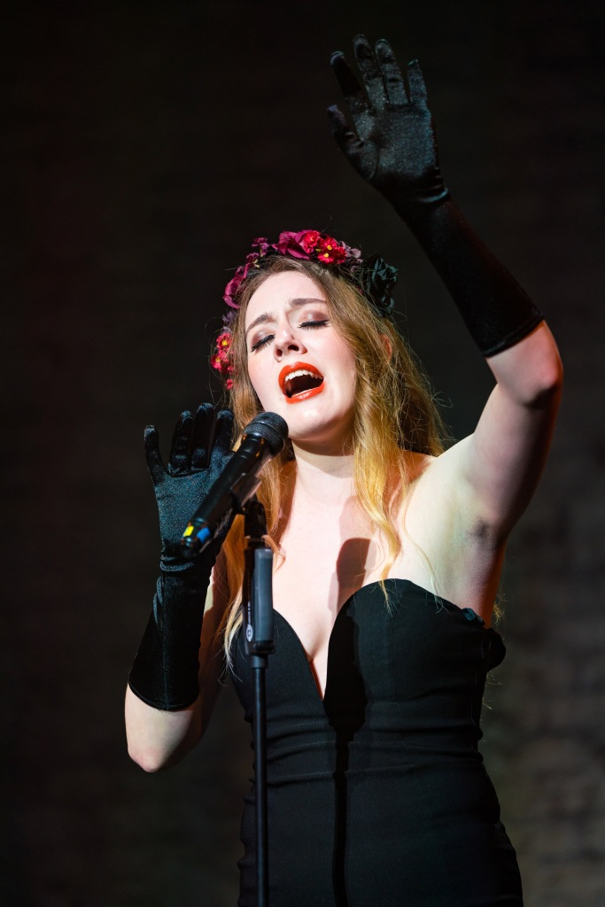 Blue Monday is a burlesque performer and musician. She is singing with her eyes closed, wearing a black strapless evening gown and elbow-length black satin gloves. Her hair is a brown-blonde and falls over her shoulders. She wears a red and black flower crown.