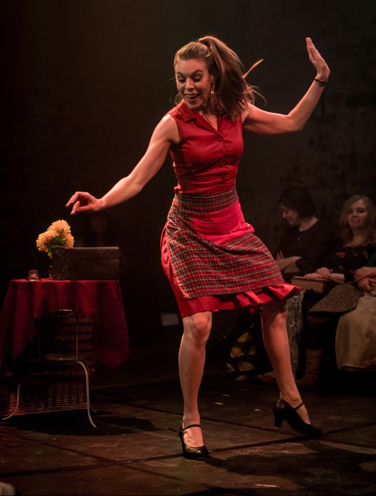 Tootsie (who also goes by Steph De Whalley) is an actress, tap dancer and cabaret performer. She is mid-tap dance here, looking cheerfully at the floor. She is wearing a red sleeveless dress, knee length, which is half-covered by a red checked apron, and black heeled tap shoes. Behind her is a table with a wrapped present and a vase of flowers on it. We can just see a couple of audience members behind her who are enjoying her dance.
