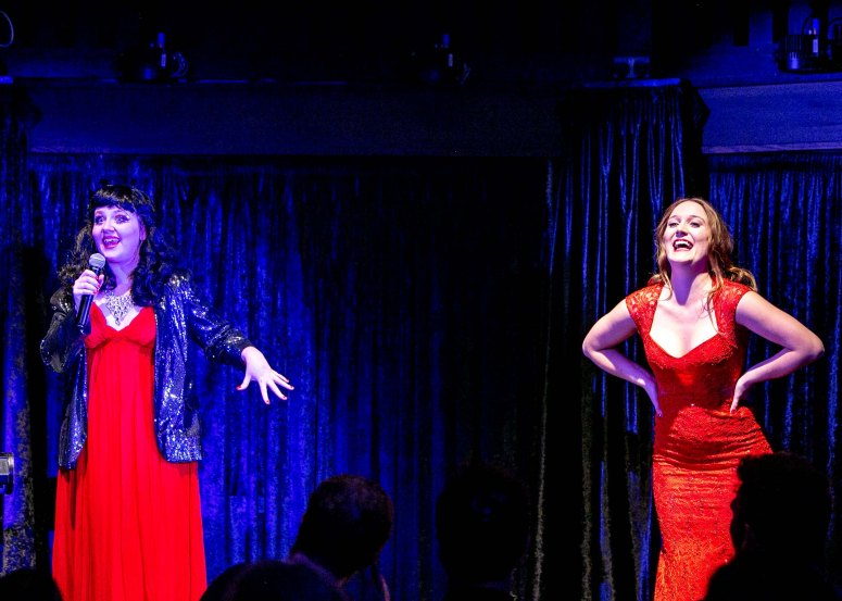 Performers Rosie Verbose and Ferrero Rochelle stand on opposite ends of the stage, both dressed in scarlet. Rosie is also wearing a black sequin blazer and a 50s-style black wig. She is holding a microphone and is saying something animatedly. Rochelle is laughing. Her auburn hair is down and her hands are on her hips.