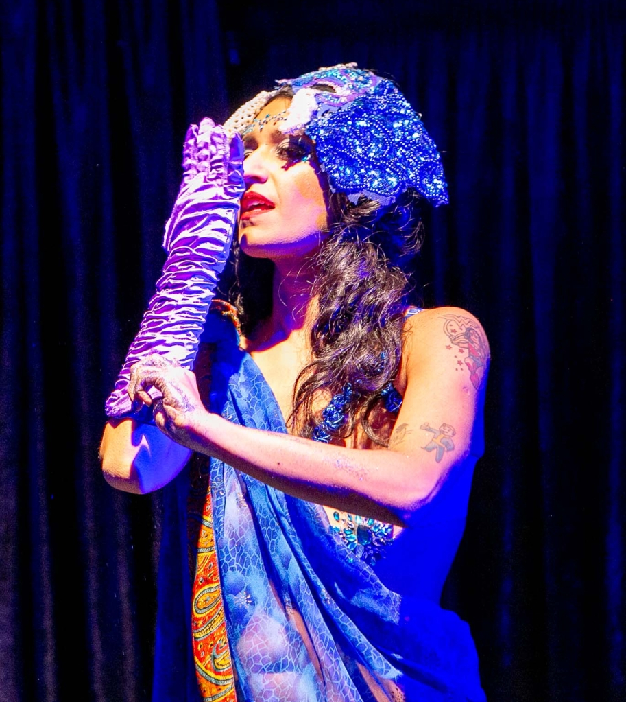 Bolly Ditz Dolly is a burlesque performer. She is dressed in a blue and orange sari and has a sequined elephant mask resting on the top of her head. She is wearing one lilac glove, which she is holding next to her face. She has long brown hair and tattoos on her exposed arm.