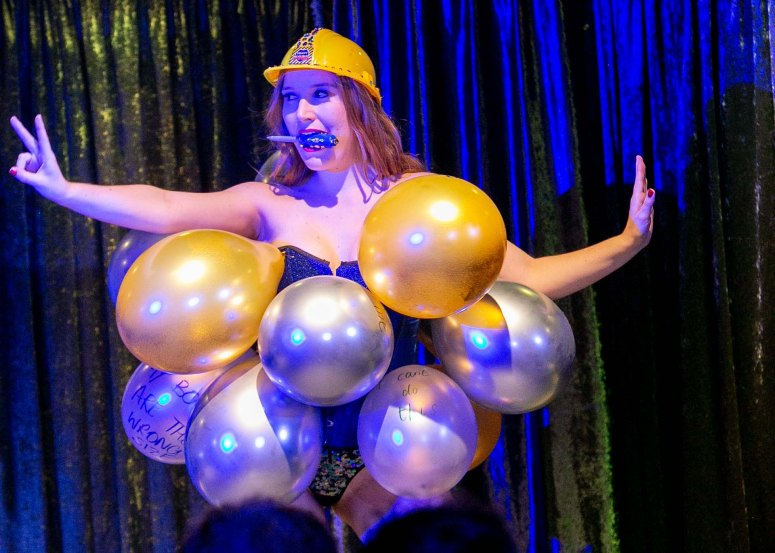 Ferrero Rochelle dancing, covered in balloons and holding a plastic screwdriver between her teeth. She is wearing a children's builder's hat.